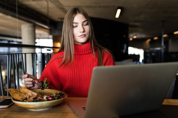 Молодая красивая женщина наслаждается салатом, сидя с ноутбуком в кафе