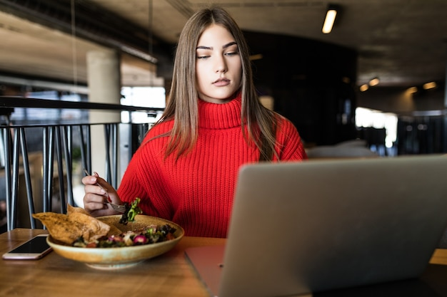 Young pretty woman enjoying salad sitting with laptop at the cafe