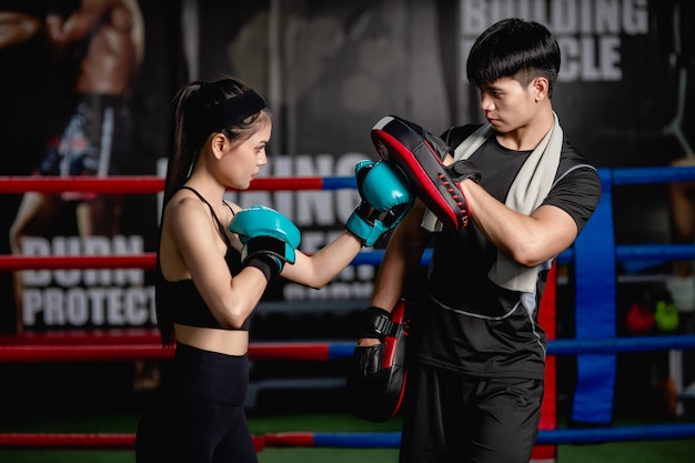 Young pretty woman exercising with handsome trainer at boxing and self defense class on the boxing ring at the gym, female and male fight acting,