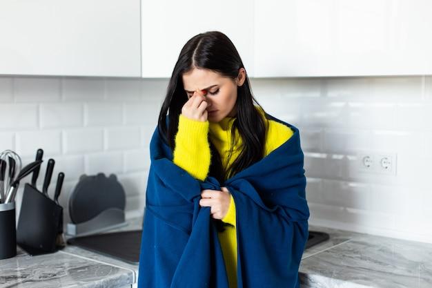 若いきれいな女性が台所で悪い病気に立ってを感じる
