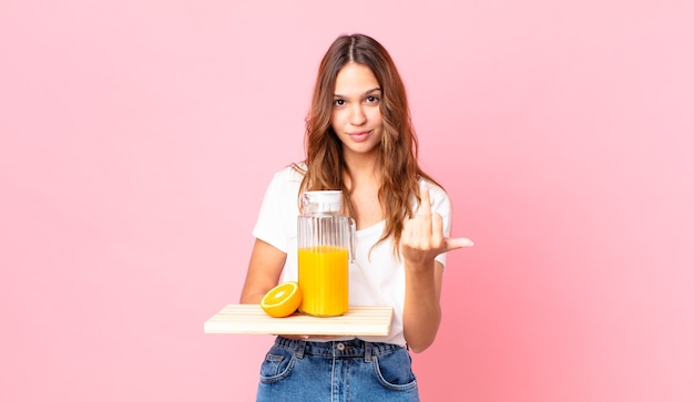 Young pretty woman feeling angry, annoyed, rebellious and aggressive and holding a tray with an orange juice