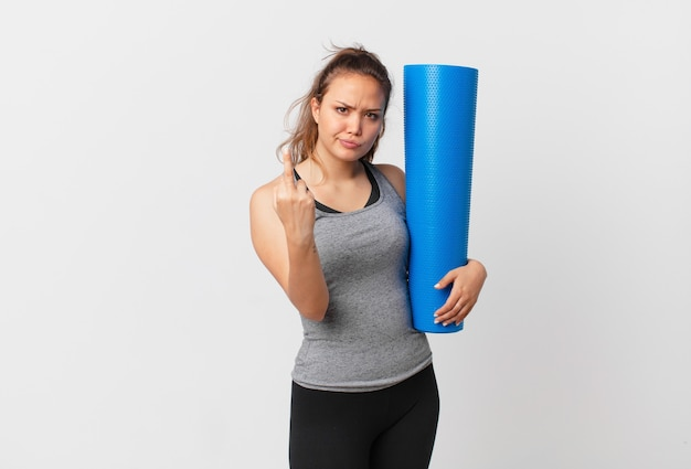 Молодая красивая женщина чувствует себя сердитой, раздраженной, мятежной и агрессивной и держит коврик для йоги