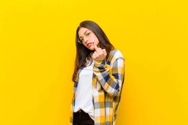 怒っている、イライラする、反抗的で攻撃的な感じの若いきれいな女性、中指を反転し、オレンジ色の壁を越えて戦う
