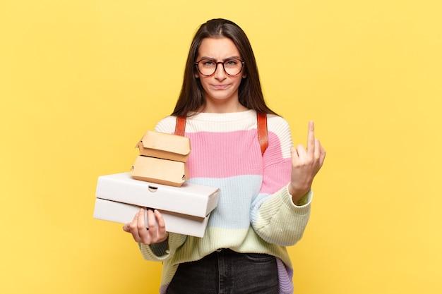 젊고 예쁜 여자는 화가 나고 짜증이 나고 반항적이고 공격적이며 가운데 손가락을 뒤집고 반격합니다. 패스트 푸드 컨셉을 잡아라