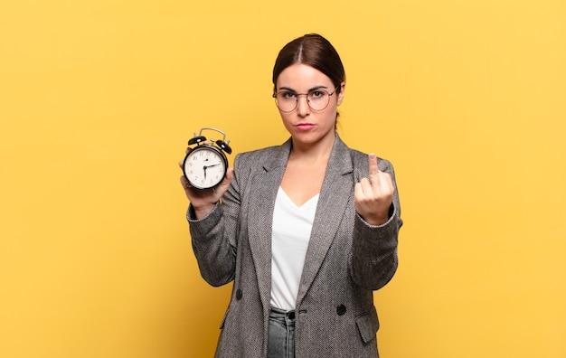 Молодая красивая женщина чувствует себя сердитой, раздраженной, мятежной и агрессивной, переворачивает средний палец, сопротивляется