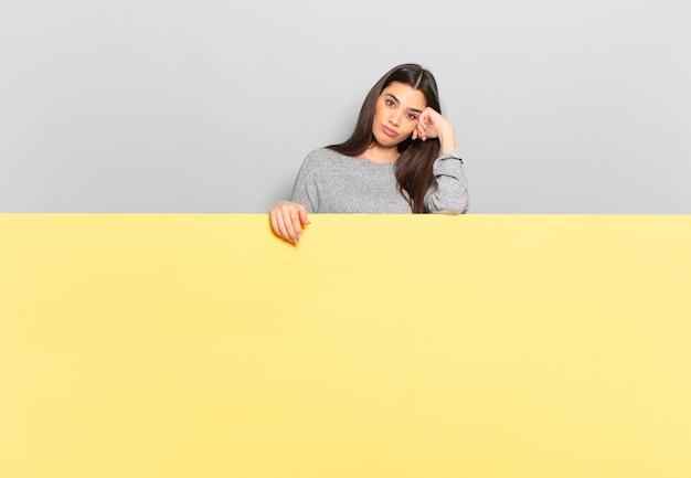 面倒で退屈で退屈な仕事をした後、手で顔を抱えて退屈、欲求不満、眠気を感じる若いきれいな女性。スペースをコピーしてコンセプトを配置します