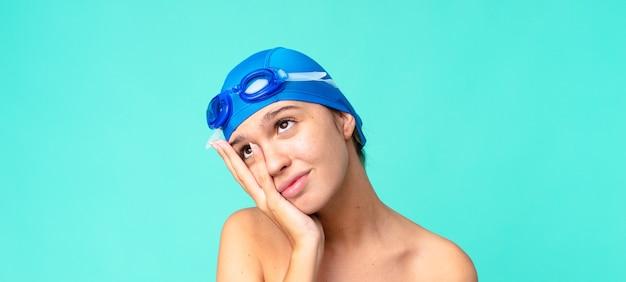 Молодая красивая женщина чувствует скуку, разочарование и сонливость после утомительной работы в очках для плавания