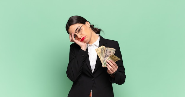 Young pretty woman feeling bored, frustrated and sleepy after a tiresome, dull and tedious task, holding face with hand. business and banknotes concept