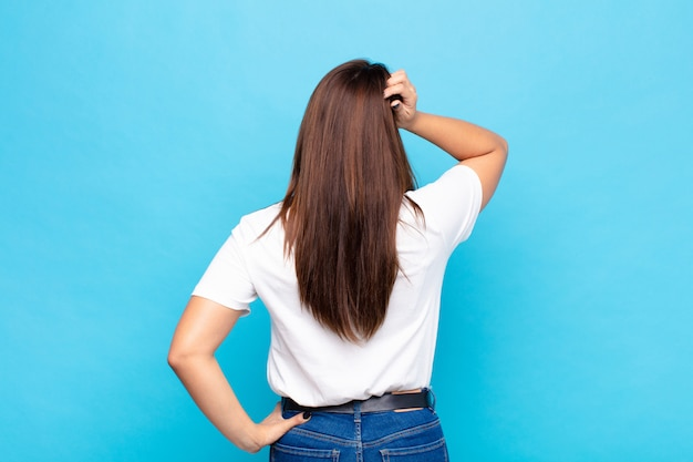 Young pretty woman feeling clueless and confused, thinking a solution, with hand on hip and other on head, rear view against blue wall
