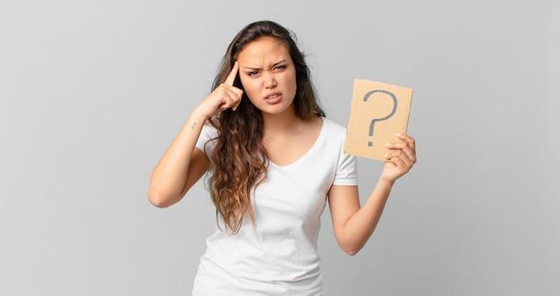 混乱して困惑している若いきれいな女性は、あなたが正気でないことを示し、疑問符のサインを持っています