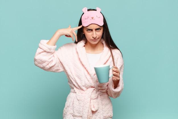 混乱して困惑している若いきれいな女性は、あなたが正気でない、狂っている、または頭がおかしいことを示しています。パジャマのコンセプトを身に着けて目を覚ます
