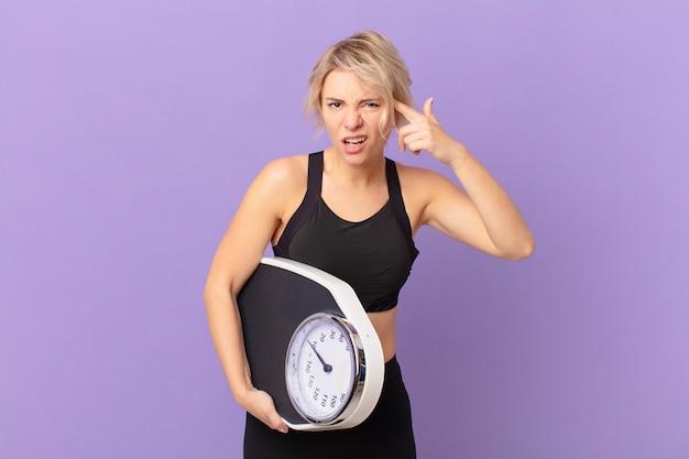 Молодая красивая женщина смущена и озадачена, показывая, что вы сошли с ума. концепция диеты