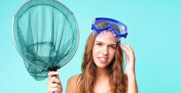 Молодая красивая женщина смущена и озадачена, показывая, что вы сошли с ума, с очками и рыболовной сетью