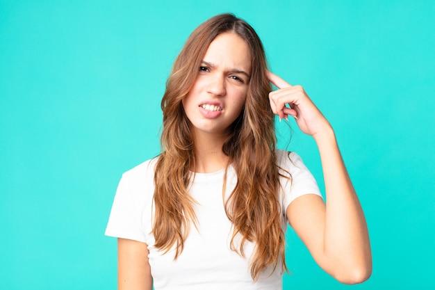 混乱して困惑している若いきれいな女性は、あなたが正気でないことを示しています