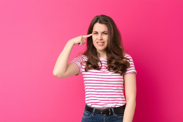 Young pretty woman feeling confused and puzzled, showing you are insane, crazy or out of your mind against pink wall