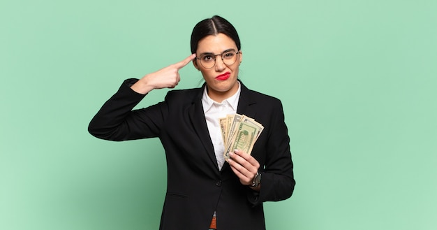 Young pretty woman feeling confused and puzzled, showing you are insane, crazy or out of your mind. business and banknotes concept Premium Photo