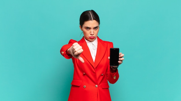 Young pretty woman feeling cross, angry, annoyed, disappointed or displeased, showing thumbs down with a serious look. smart phone concept