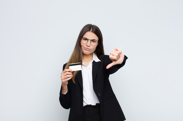 Young pretty woman feeling cross, angry, annoyed, disappointed or displeased, showing thumbs down with a serious look with a credit card
