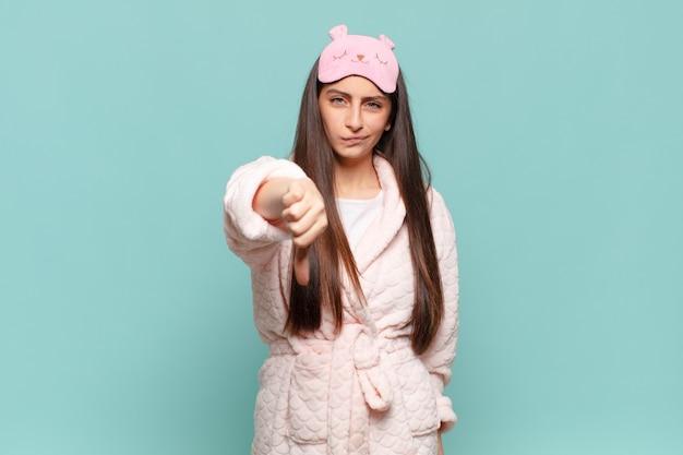 젊은 예쁜 여자는 십자가, 화난, 짜증, 실망 또는 불쾌감을 느끼며 진지한 표정으로 엄지손가락을 아래로 내보입니다.