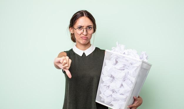 Молодая красивая женщина, чувствуя крест, показывает палец вниз. бумажные шары мусор концепция