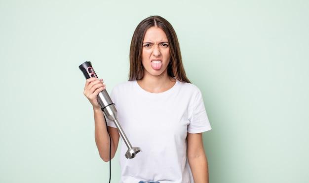嫌悪感とイライラを感じ、舌を出す若いきれいな女性。ハンドミキサーのコンセプト
