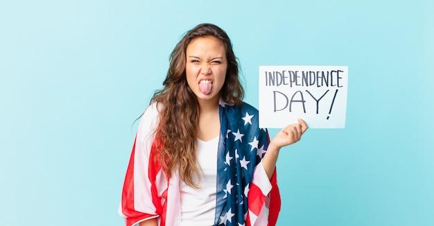 うんざりしてイライラし、独立記念日のコンセプトを舌で感じる若いきれいな女性