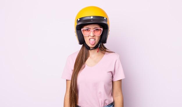 젊은 예쁜 여자는 역겹고 짜증이 나서 혀를 내밀고 있습니다. 오토바이 라이더와 헬멧