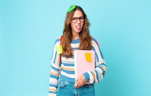 うんざりしてイライラし、鞄を持って本を持って舌を出す若いきれいな女性
