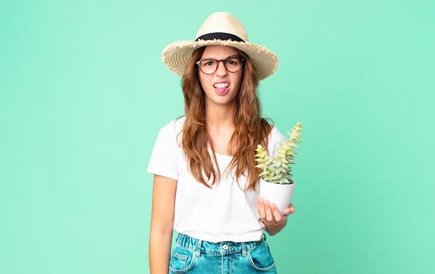 Молодая симпатичная женщина чувствует отвращение и раздражение, высовывает язык в соломенной шляпе и держит кактус