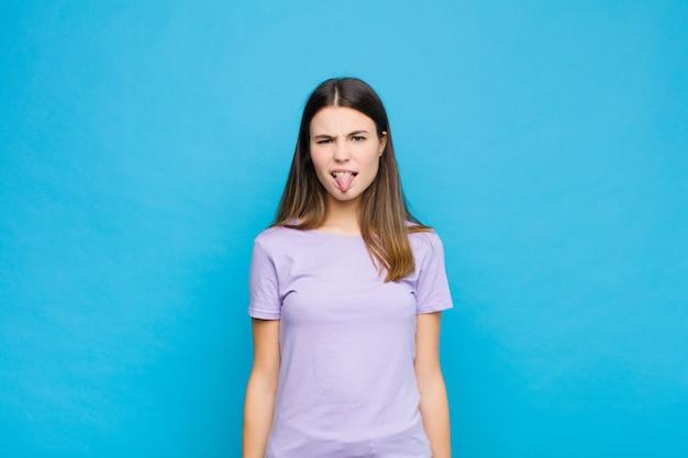 Молодая красивая женщина чувствует отвращение и раздражение, высунув язык, не любит что-то противное и противное у синей стены