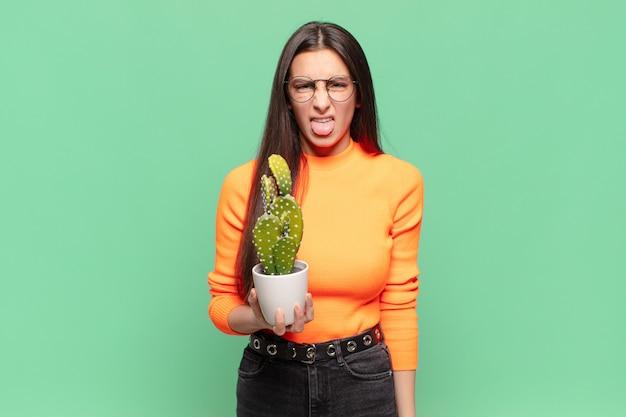 Молодая симпатичная женщина чувствует отвращение и раздражение, высовывает язык, не любит что-то противное и противное. концепция кактуса