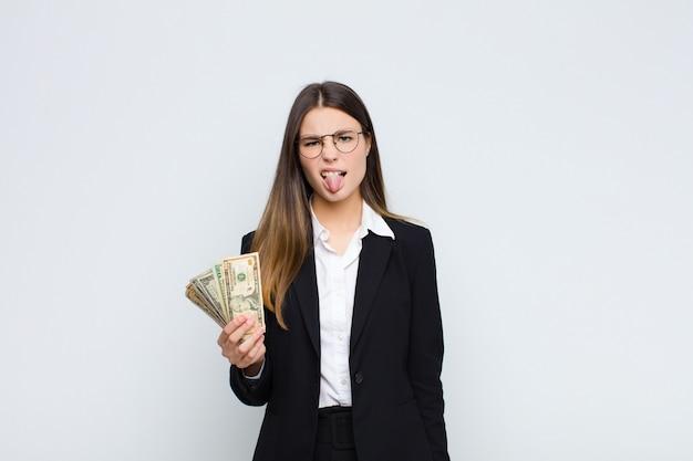 Молодая красивая женщина чувствует отвращение и раздражение, высовывает язык, не любит что-то противное и противное с банкнотами