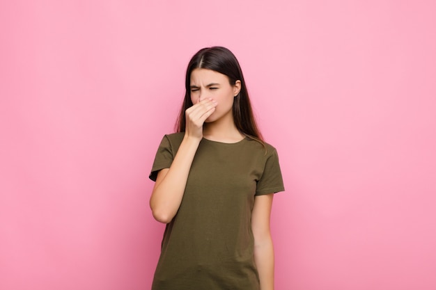 Young pretty woman feeling disgusted, holding nose to avoid smelling a foul and unpleasant stench against pink wall