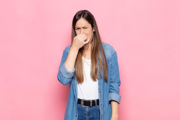 嫌悪感と不快な悪臭を嗅ぐのを避けるために鼻を保持している若いきれいな女性