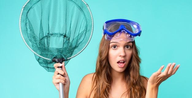 Молодая красивая женщина чувствует себя чрезвычайно шокированной и удивленной с очками и рыболовной сетью