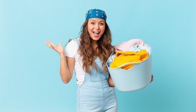 信じられないほどの何かに幸せと驚きを感じ、洗濯かごを持っている若いきれいな女性