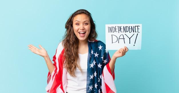 信じられないほどの独立記念日のコンセプトに幸せと驚きを感じている若いきれいな女性