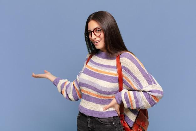 젊은 예쁜 여자는 행복하고 쾌활한 느낌, 미소하고 당신을 환영하며, 친절한 제스처로 당신을 초대합니다. 학생 개념