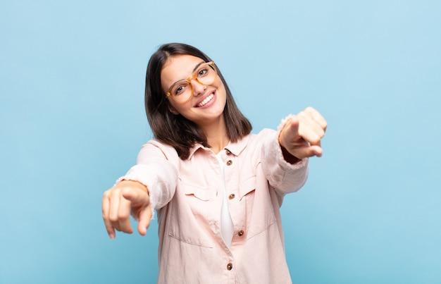Молодая красивая женщина чувствует себя счастливой и уверенной, указывая на камеру обеими руками и смеясь