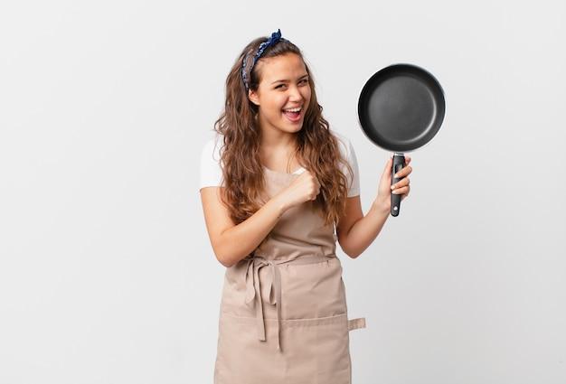 幸せを感じ、挑戦に直面したり、シェフのコンセプトを祝って鍋を持っている若いきれいな女性