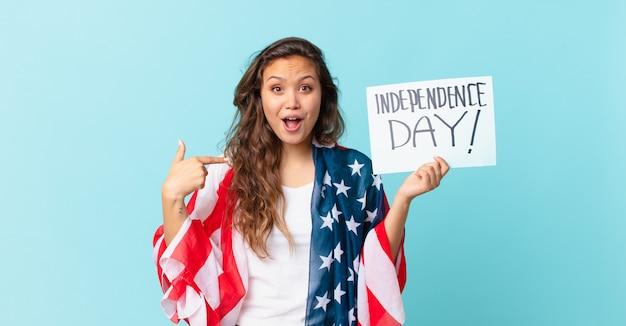 幸せを感じ、興奮した独立記念日のコンセプトで自己を指している若いきれいな女性