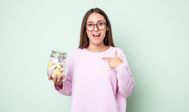 幸せを感じ、興奮して自分を指している若いきれいな女性。ゼリーキャンディーのコンセプト