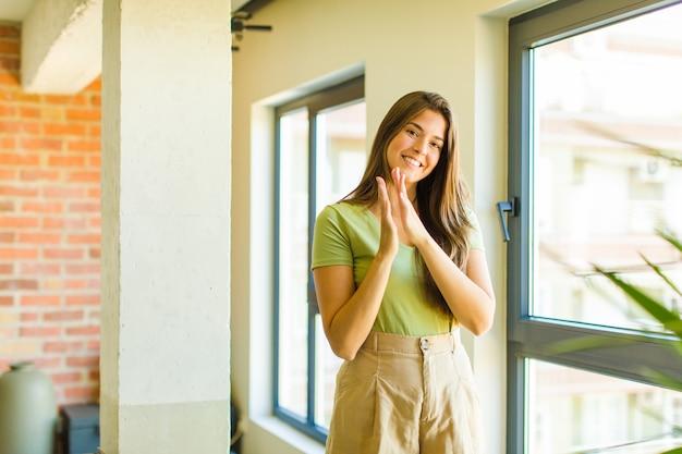 幸せで成功を感じている若いきれいな女性