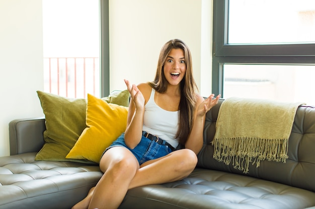 Молодая симпатичная женщина чувствует себя счастливой, удивленной, удачливой и удивленной, вроде серьезно говорит: «боже»? невероятно