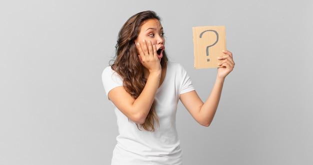 젊고 예쁜 여자는 행복하고 흥분되고 놀라며 물음표 기호를 들고 있다