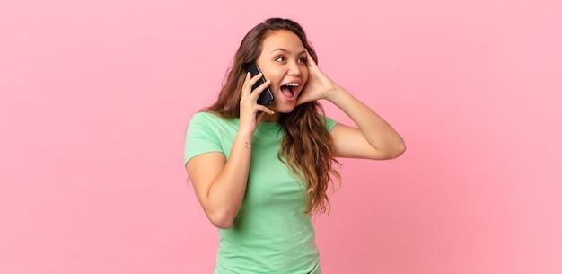 젊고 예쁜 여자는 행복하고 흥분되고 놀라며 스마트 폰을 들고 있다