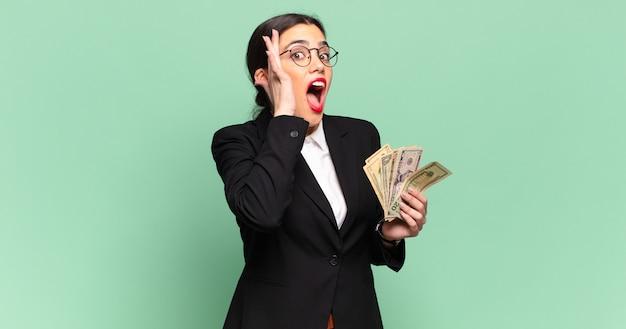 Молодая красивая женщина чувствует себя счастливой, взволнованной и удивленной, глядя в сторону обеими руками на лице. концепция бизнеса и банкнот