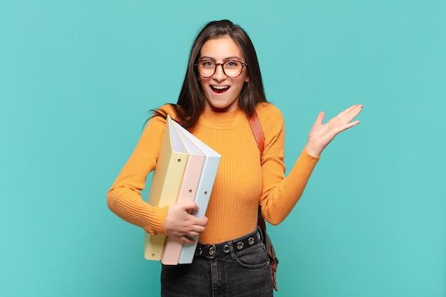 행복, 흥분, 놀라움 또는 충격을 느끼고 웃고 믿을 수없는 것에 놀란 젊은 예쁜 여자. 학생 개념