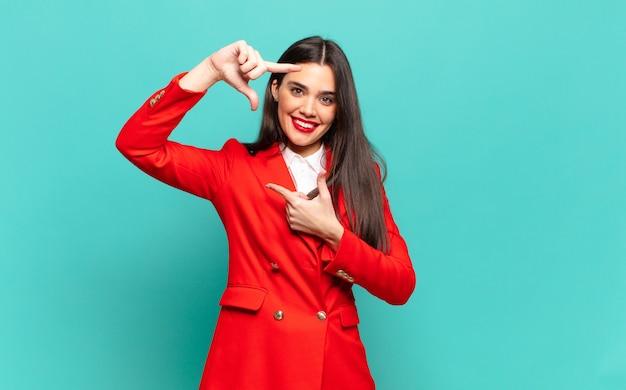 Молодая красивая женщина чувствует себя счастливой, дружелюбной и позитивной, улыбается и делает руками портрет или фоторамку. бизнес-концепция