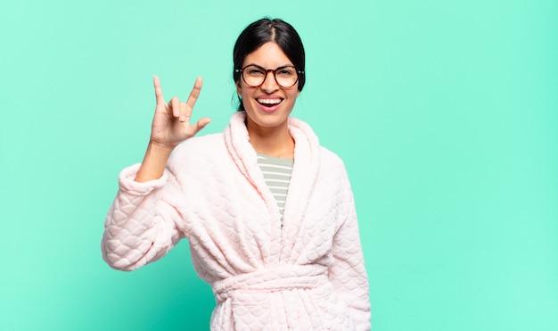 Молодая красивая женщина чувствует себя счастливой, веселой, уверенной, позитивной и мятежной, делая знак рок или хэви-метал рукой. концепция пижамы
